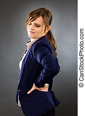 Portrait of a young businesswoman with back pain isolated...