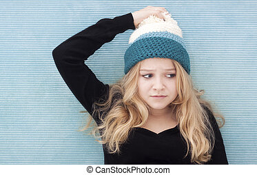 confused teenage girl - A pretty young woman with a woolly...