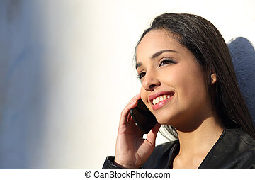 Beautiful woman talking and smiling happy on the mobile phone in a sunny day against a white wall
