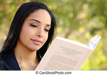 Close up of a beautiful woman reading a book in a park