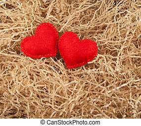 Red hearts - Two felt red hearts on the sawdust