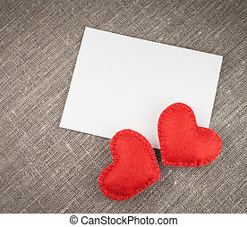 Red hearts and label on linen background.