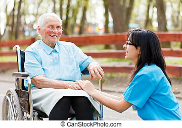 Chatting with Elderly Lady - Kind nurse holding elderly...