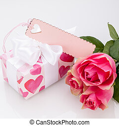 Gift box with an empty tag, next to three roses - Close-up...