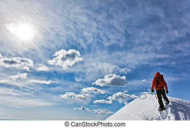 Reaching the summit - Mountaineer reaching the top of a...