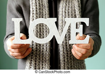 man holding the wooden word love