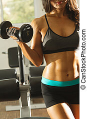 Torso of a young fit woman lifting dumbbells