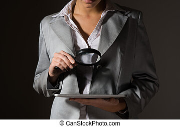 business woman holding a magnifying glass