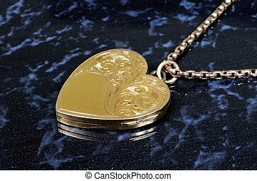 Heart shaped gold locket - Heart shaped gold locket against...