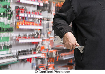 shoplifter at work - male shoplifter stealing tools in a...