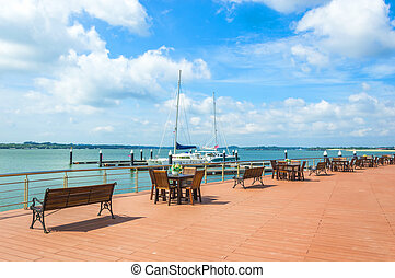 View of wooden table and chair at outdoor cafe with yatch...