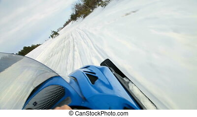 Snowmobile racing - Riding snowmobile along snowy track POV