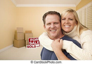 Couple in New House with Boxes and Sold Sale Sign - Happy...