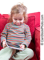 Adorable shy little girl with a tablet-pc in her hands...
