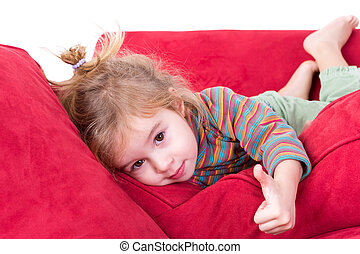 Beautiful little girl giving a thumbs up gesture as she lies...