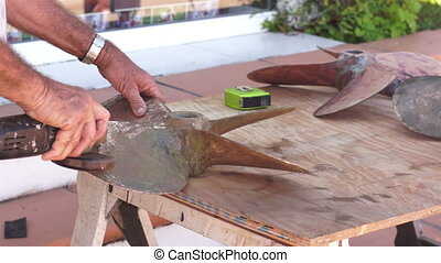 Industrial Boat Prop Restoration - A man grinding the...