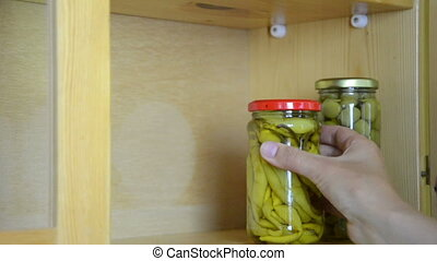 jar pepper olive - hand puts one after the other jars with...