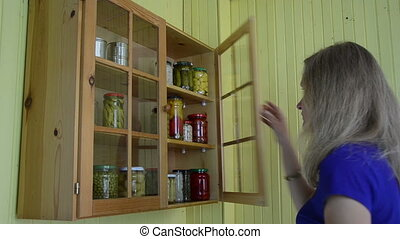girl cabinet pickled food - Girl woman take glass jar with...