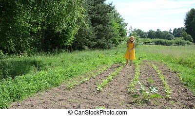 girl hoe grub weeds - Barefoot farmer girl in yellow dress...