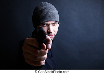 Portrait of a man holding gun against a black background