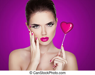 Beauty Woman Portrait. Beautiful Fashion Model Girl holding red heart. Perfect Skin. Make up. Isolated on purple Background.