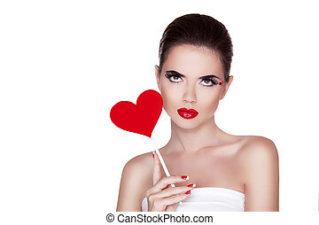 Beauty portrait of sexy cute girl with bright makeup holding red heart isolated on white background. Manicured nails and Red Lips.