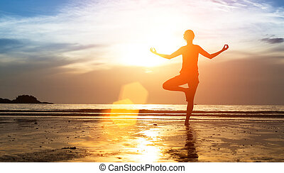 Silhouette of woman practicing yoga at sunset.