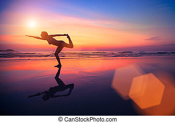 A silhouette of a woman practicing yoga on the beach at sunset.