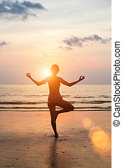 Silhouette of a beautiful yoga woman on the beach at sunset.