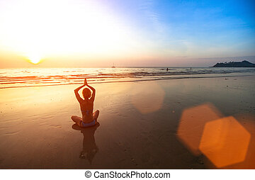 Young woman meditating on the beach at sunset.