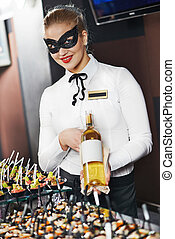 Waitress girl in mask with bottle