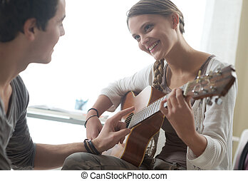 Learning the guitar - Young beautiful couple resting at home...