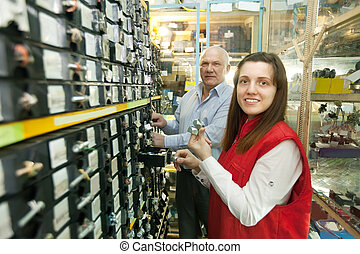 People chooses fasteners in auto parts store