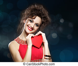 Girl in red dress keeps the heart. Concept of Valentine's...