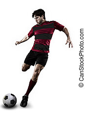 Soccer player in a red and black uniform kicking. White...