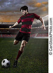 Soccer player in a red and black uniform kicking on a...