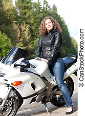 woman sitting on a motorcycle - beautiful young female biker...
