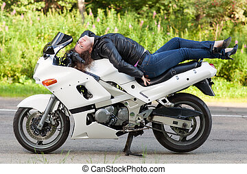 woman lies on a motorcycle - young beautiful woman lying on...