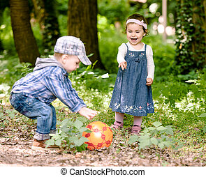 Boy and girl are playing with ball outdoor