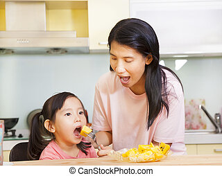 Mother feeding daughter eating fruits in the kitchen