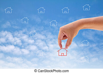 Hand select home symbol on blue sky