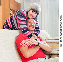 Loving ordinary senior couple together in home interior