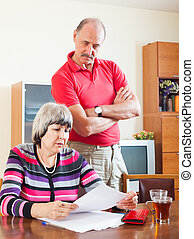 mature couple reading financial document - serious mature...