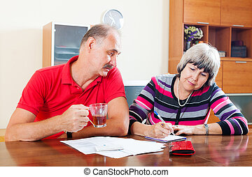 mature couple fills in questionnaire together at home