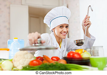 Happy cook in toque works at kitchen - Happy female cook in...
