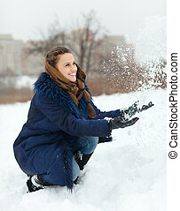 Happy girl throwing up snowflakes in wintry park
