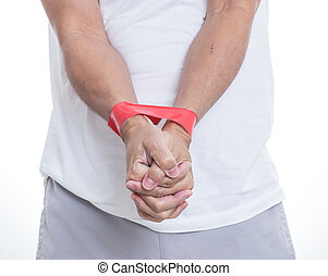 Man hands bound by red tape