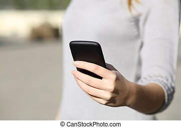 Woman hand holding and browsing a smart phone outdoor -...
