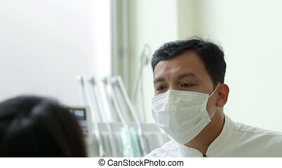 Dentist visiting patient - Asian dentist visiting young...