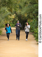 Jogging in a park - Active people jogging in a  lush park